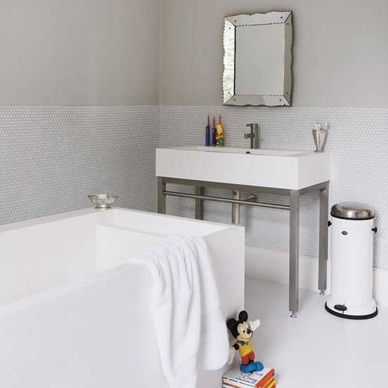 This family bathroom combines practicality and style. A 1930s mirror adds a touch of elegance to the all-white scheme.    The Puro bath and basin are by Arup Associates from Durat. The bin is by Vipp. Find a mirror in this style at Graham & Green. The Metro tiles are from Homebase.    Chosen by Livingetc    Photograph by Andreas Von Einsiedel