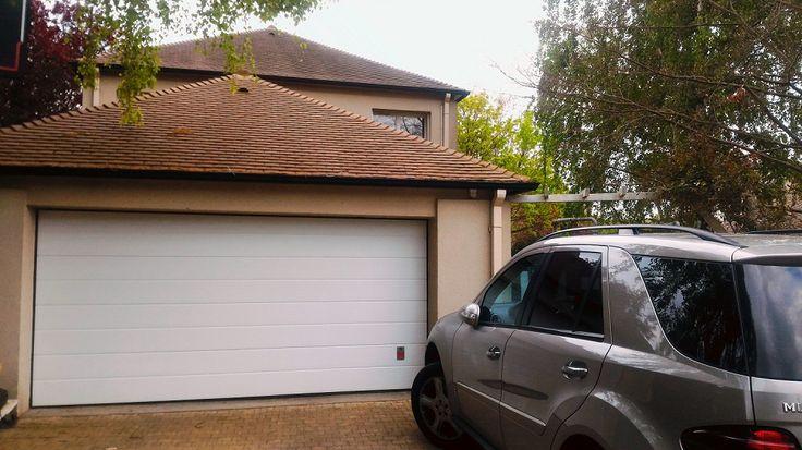 Porte de garage sectionnelle blanche mono-rainurée chez M. et Mme D à BUSSY SAINT GEORGES (77)