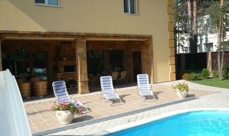 Во внутреннем дворе сделали патио с бассейном. Вокруг бассейна вымощена площадь плиткой. Дополняют дизайн патио цветы в горшках.