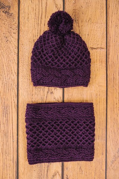 Lush, three-dimensional texture is the name of the game in this sweet hat and cowl set. Hat brim and cowl borders are worked sideways while the crossed lattice pattern is worked vertically. Complete with a pom pom that reminds us of a sugar plum, this is the set you should make this season.