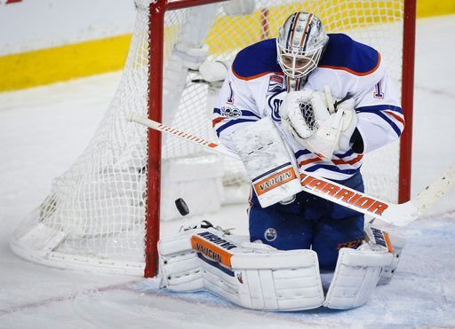 Edmonton Oilers goalie Laurent Brossoit stares down at the puck during the third period of the team's NHL hockey game against the Calgary Flames on Saturday, Jan. 21, 2017, in Calgary, Alberta. (Jeff McIntosh/The Canadian Press via AP)