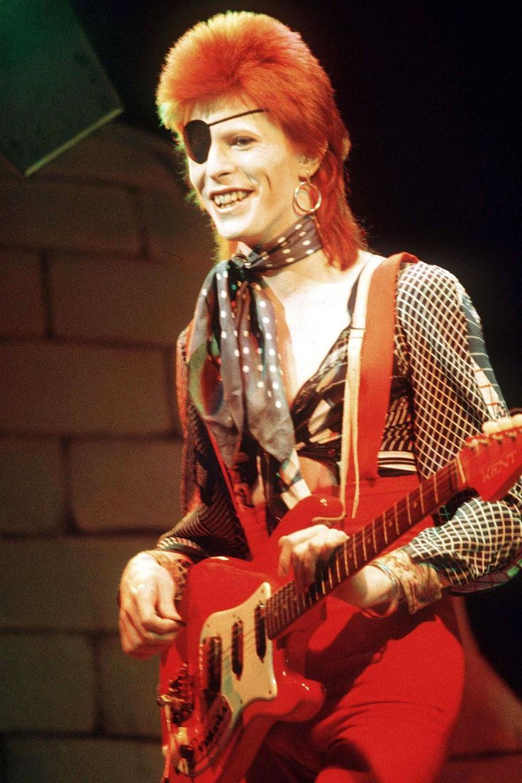 David Bowie performing on stage in an open shirt and red trousers, Halloween…