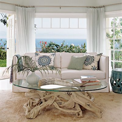 Cool and Calm The driftwood coffee table is a bold focal point that references the natural environment outside. Neutral colors with accents of cool blues and green create a calming coastal atmosphere.