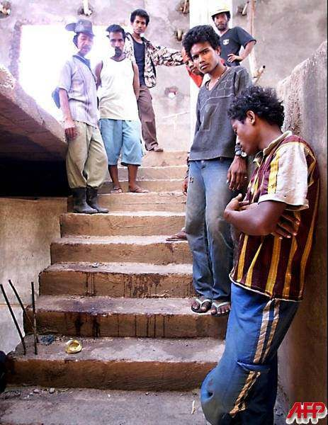 SUAI, EAST TIMOR, 16-OCT-1999: East Timorese men stand on the blood   stained steps of the unfinished Suai Cathedral October 16 1999. About   200 people were allegedly killed in the Suai church compound by   militias and Indonesian soldiers during a September 6 1999 attack,   according to an eyewitness. The International Force for East Timor   (INTERFET) said they would investigate the incident. [Photo by Romeo   Gacad, AFP]