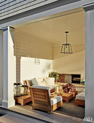 The loggia of this Hamptons home, designed by Brian Sawyer, is outfitted with a built-in fireplace, plus pendant lights, seating, tables, and a rug, all by RH | archdigest.com