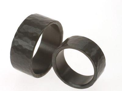 Zwarte ringen met hamerslag.Een bijzonder oppervlak hebben deze ringen: Een structuur van grove hamerslag. Breedte van de ring(en) kan naar wens aangepast worden. Op de afbeelding zijn de ringen 8 en 9.5 mm.