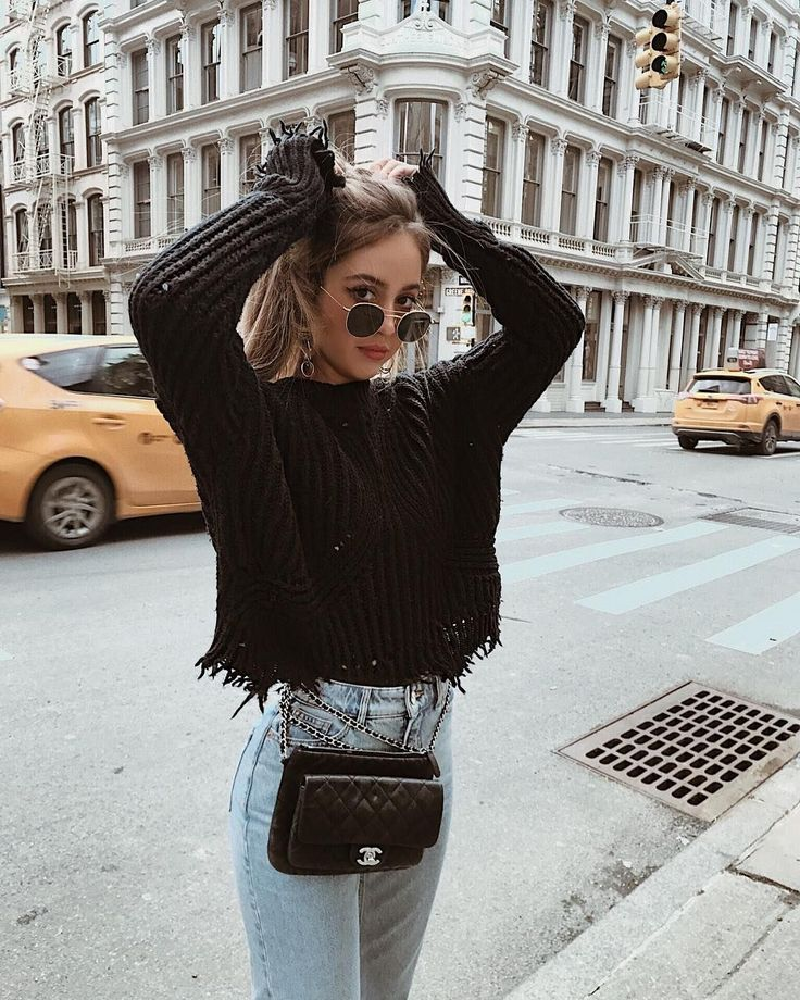 Trendy frayed black knit sweater with high waisted denim jeans.