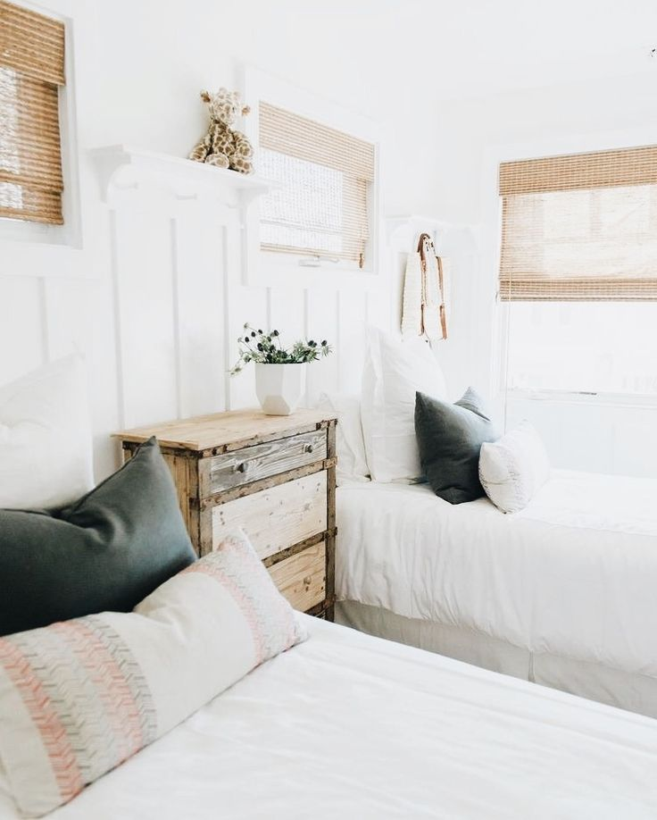 Super chic white bedroom with wood blinds, and charcoal pillows