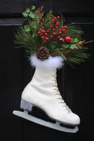 Hanging ice skate on front door decorated with Christmas greenery
