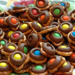 Want to make these little delicious treats? Just melt Hershey's kisses onto tiny twist pretzels (275 degrees, 3 minutes), remove, and immediately press a single m&m; on each. Refrigerate until eating to make sure they are deliciously solid!