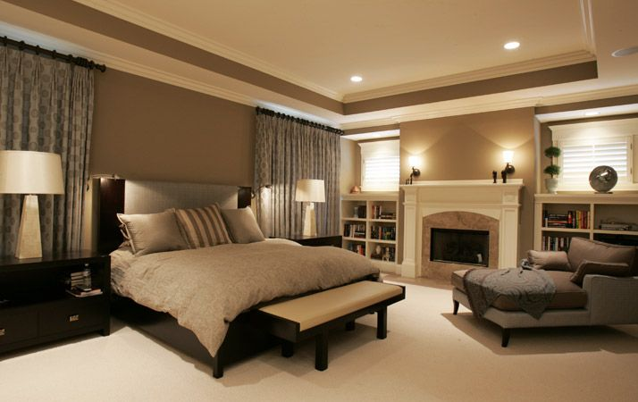 Gorgeous neutral master bedroom with fireplace, curtains and built ins