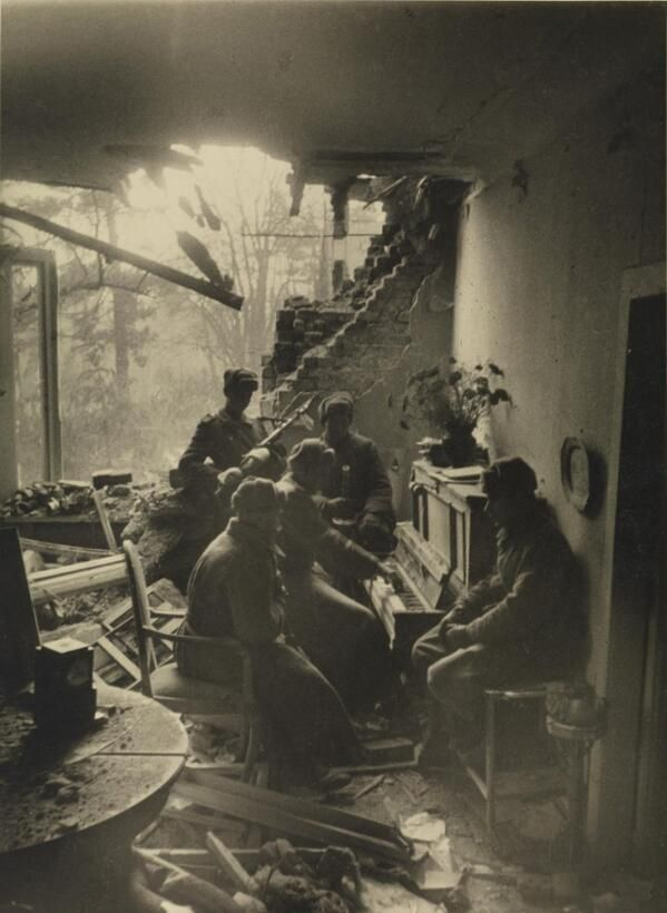 Russian soldiers playing piano in a wrecked living room in Berlin, 1945. By Dmitri Baltermant