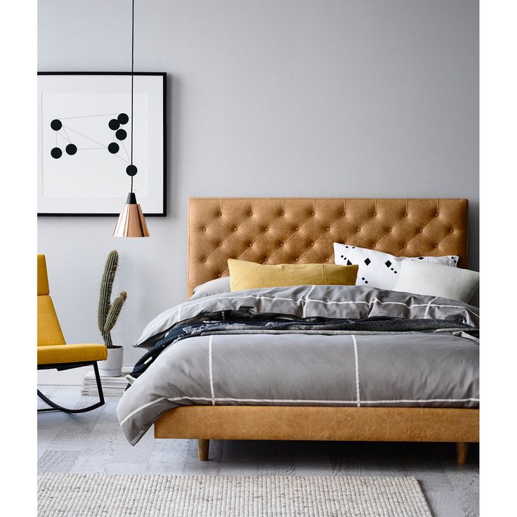 Grey walls, tan leather bed, wood furniture, indigo accessories, black and white art                                                                                                                                                     More