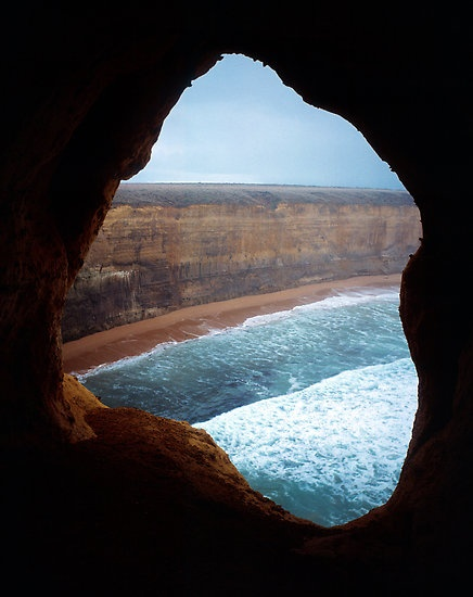 Apostles Cave by Ern Mainka  Looking out from a cave on an eroding peninsular which will eventually become another free standing stack (or apostle). One step further back and it's a very high plunge into the ocean. This section is now closed to the public due to erosion and obvious safety reasons. Taken c 1980.  'The Twelve Apostles', Great Ocean Road coastline, Port Campbell National Park, Victoria, Australia.