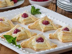Thanks to shortcuts like frozen puff pastry, we're able to make jaw-dropping pastries like our Raspberry Cream Danish. These are filled with a homemade cream cheese filling, which makes them extra-special. A raspberry in the center and a sprinkle of powdered sugar are the finishing touches to this bakery-style treat.