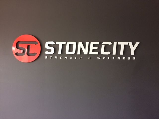Speedpro Signs Kingston completed this channel lettering for Stonecity. The circle is custom coloured red with SC cut out to show the wall behind it. STONECITY is stud mounted to stand off the wall.  Strength & Wellness are flush mounted to the wall and letters are white for contrast. Impressive!