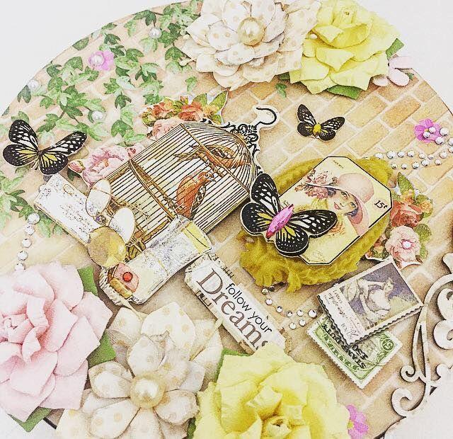 layout na tampa de mdf redondo decorado com adesivos, papéis, flor artesanal e atrass