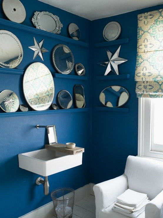 Blue bathroom with multiple mirrors and great blind.