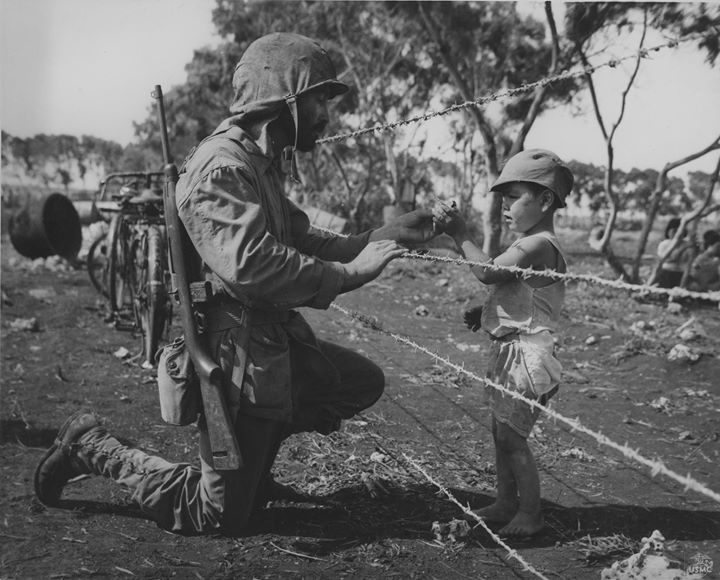 US Marine giving an interned child candy Tinian Mariana Islands 1944.