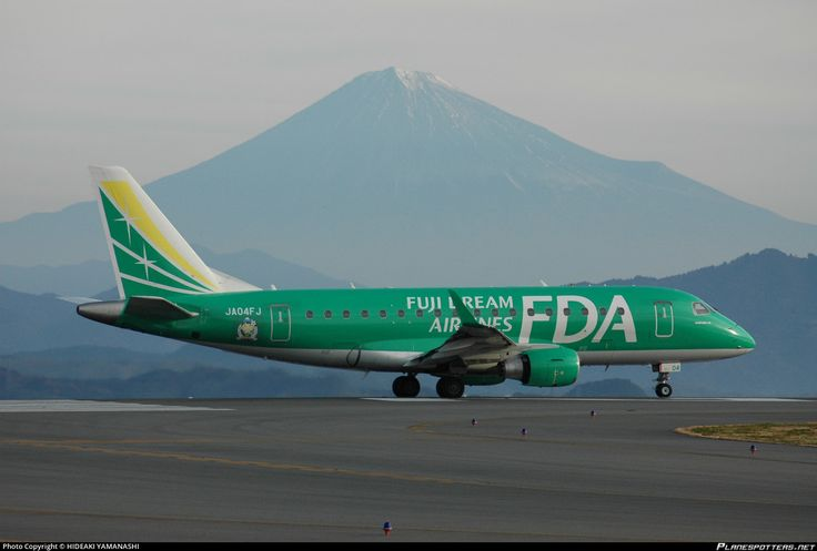 Fuji Dream Airlines-FDA (JP) Embraer ERJ-170 JA04FJ aircraft, with the mascot of the 100th anniversary of the enforcement Matsumoto municipality ''ARUPU-CHAN'' on the airframe, skating at Japan Shizuoka (Mt Fuji) Airport. 01/01/2012. (Mt. Fuji in the background). (The Green colored plane).(Matsumoto=a city located in Central Nagano prefecture).
