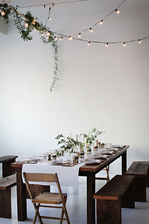 Twinkle lights, greenery and wood benches