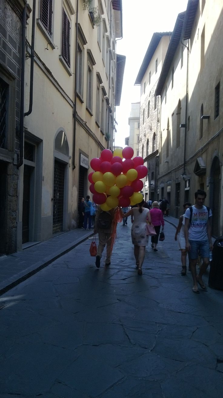 Woman carrying balloons in a street in Firenze.