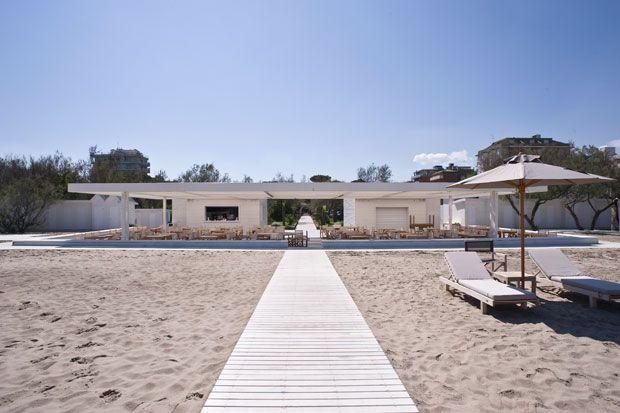 Un pergolato in legno bianco ripara dal sole i tavoli del ristorante e bar sul mare
