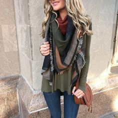 Beautiful fall look with layers of deep colors: green sweater, multicolored scarf and red-brown purse.