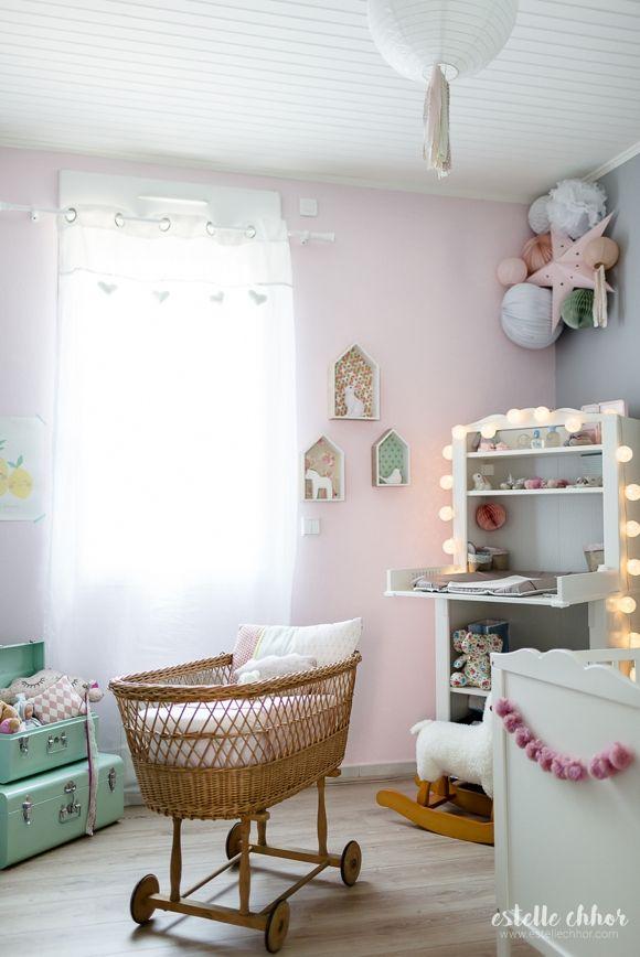 Une chambre bébé aux murs roses et avec un lit bébé en rotin