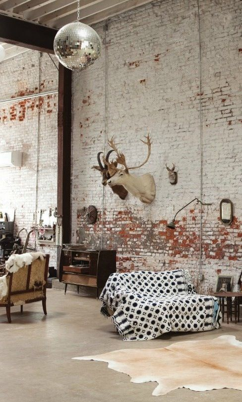 Exposed brick wall mixed with textiles and warm wood. Gorgeous.