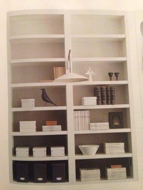 En helt vanlig vit bokhylla (tänk Ikeas Billy eller Expedit) som fått bakstyckena målade i olika grå toner. Mörkare fält nertill och ljusare allt längre upp i hyllan man kommer.