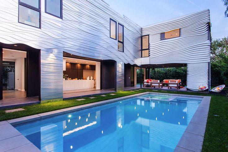 Le patio avec sa grande piscine extérieure devient le cœur de cette belle demeure de ville