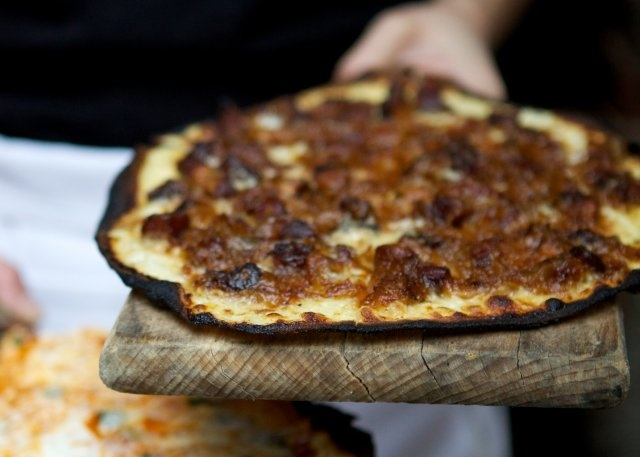 An Alsatian pizza, or tarte flambé, with onions, bacon and cheese. It ...