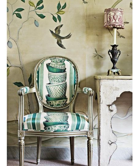 dining room chair covered with Pierre Frey's Ming, which Nicky Haslam sprayed with tea to soften its whites. What looks like wallpaper is actually a hand-painted replica—complete with seams and torn edges—of a paper John Fowler used: