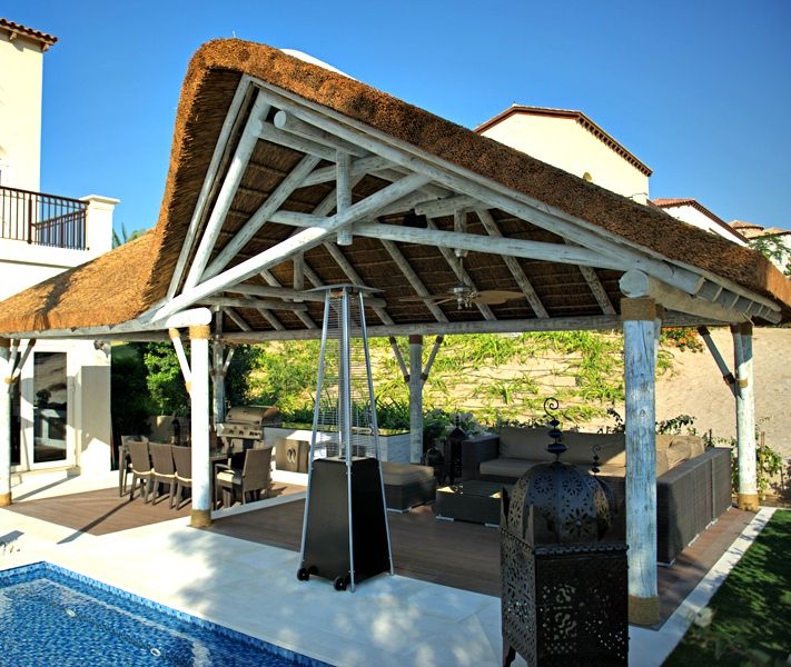 Outdoor living space with whitewash thatched gazebo and outdoor kitchen!
