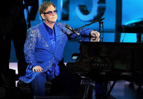 """In honor of HBO's Liberace film """"Behind the Candelabra"""", co-stars Matt Damon and Michael Douglas introduced Elton John to pay a musical tribute to the legend at the 2013 Emmy Awards. In his first appearance on the Emmys, E.J. donned a blue sequined jacket and thanked Liberace for his musical and fashion inspiration, and played a new ballad called """"Home Again"""" that he co-authored with Bernie Taupin."""