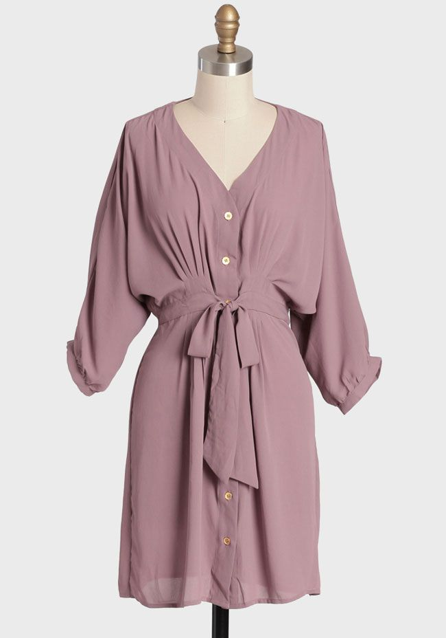 Demure Darling Shirt Dress In Lavender $42.99 at shopRuche.com. This classic semi-sheer dusty lavender shirt dress features contrast  gold-toned front button closures and a self-tie bow at the waist for a  flattering silhouette. Finished with an asymmetrical hem and subtle  pleated detailing for...