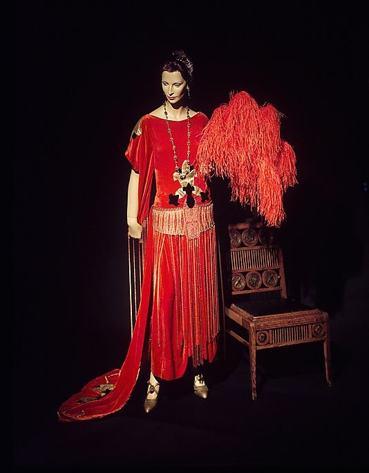 "1921 ""Robe Sabat"" dress by Paul Poiret.  Poiret's cultural fascination can be seen in this dress, which is named for the historical Middle Eastern kingdom, Sheba. The beadwork belt and fringe assist in evoking the exotic feel while the fleur-de-lis puts the gown in a national context."