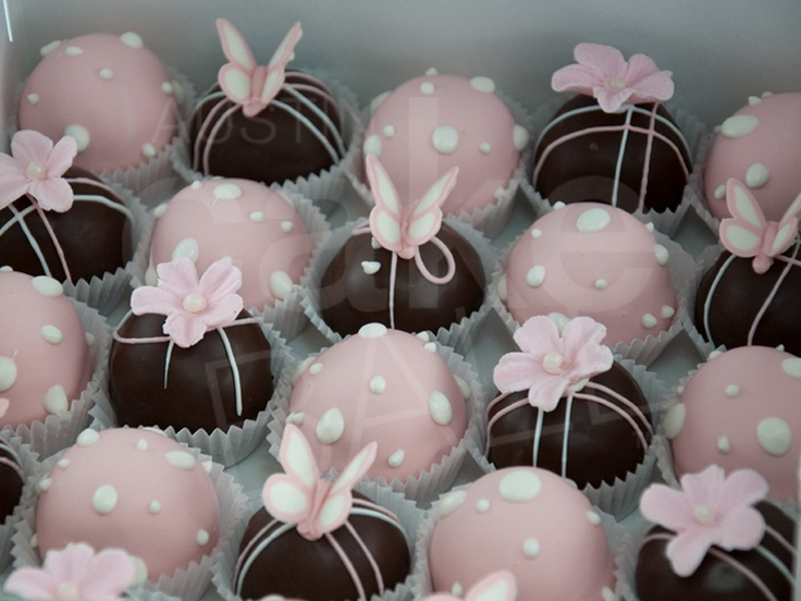 Pink polka dot cake balls with butterflies for a baby shower.