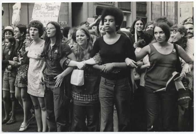 A group of young white and black women stand together, smiling, at a protest in 1970