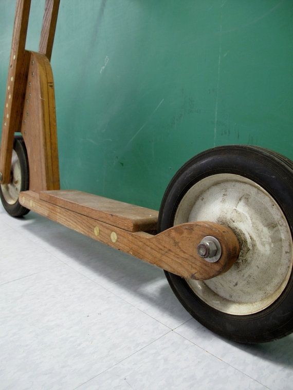 This is a very cool vintage push scooter, possibly from a Popular Mechanics / Popular Science set of plans. It appears to be home-made, but constructed very well given that. Made of solid oak, heavy duty hardware and hard rubber and steel wheel set, this scooter held up to the toll any young rider could give. Definitely a one-of-a-kind piece perfect for any vintage bike or toy collector, or as a very cool wall-hanger.    Appropriate vintage age and wear, signs of normal use. Circa 1950s-...