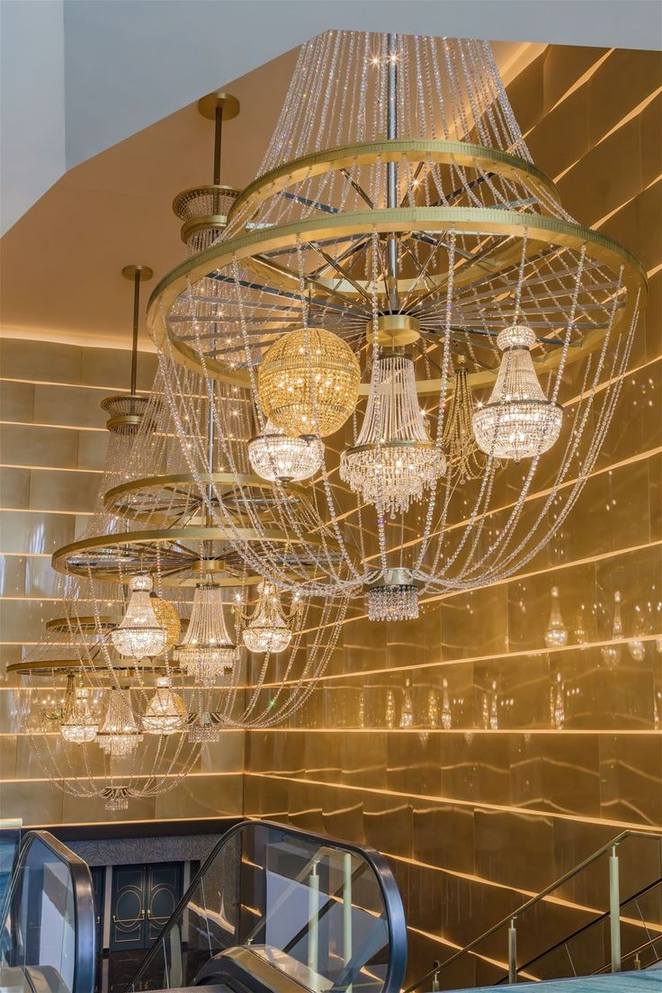 On guard over the lobby in the Park Theater at Monte Carlo in Vegas stand our three gigantic chandeliers. Each weighs 1,5 ton and encompasses five individual smaller chandeliers - one of the biggest technological challenges solved by our technicians. #design #light #lighting #chandelier #elegance #hotel #hospitality #lobby #lobbylighting