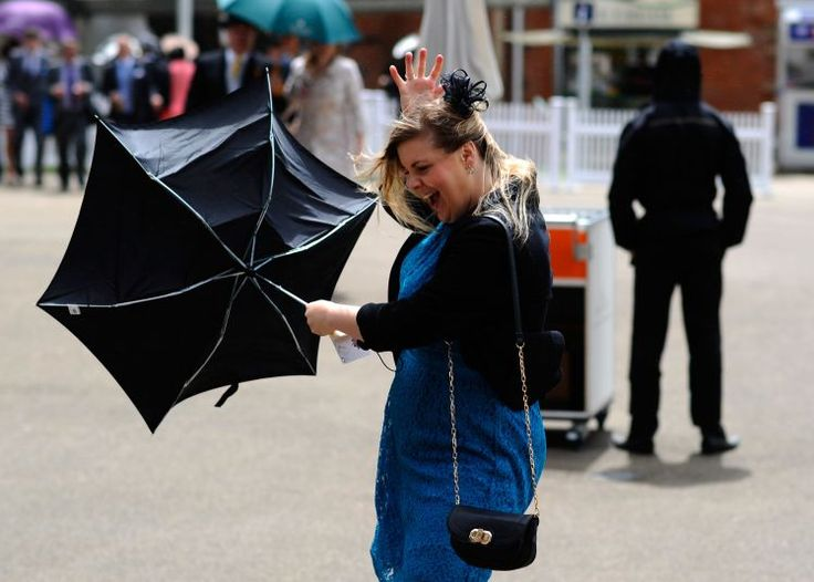 A racegoer loses control of her umbrella in a strong gust of wind (Picture: Getty)