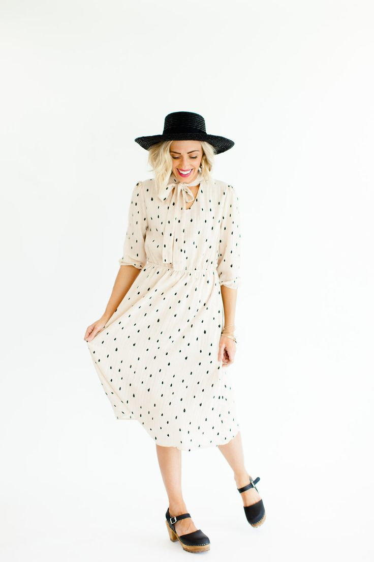 "Blush Polka Dot Midi Dress Sheer 3/4 Sleeves + Elastic Cuff V-Neck + Ribbon Necktie Fully Lined Bodice + Skirt Black Brush Stroke Print Gathered Elastic Waist View Size Chart Model is 5'7"" + Wearing a Small"