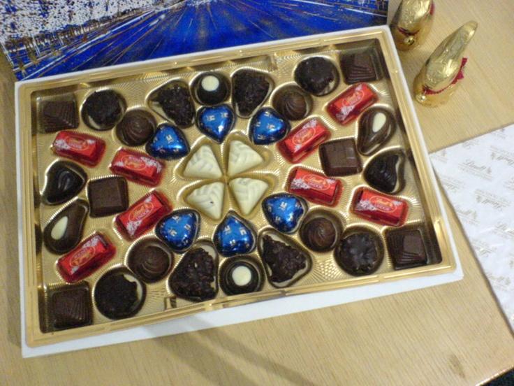 A l'intérieur de la boîte, on constate que certains chocolats possèdent un packaging primaire. Ils sont emballés dans une fine pellicule de couleur. Il s'agit en fait de classiques de la marque Lindt, disponible dans le commerce sous de plus grands formats comme le Coeur de lait ou le Lindor. On remarque aussi l'intérieur doré qui compose le packaging secondaire et qui rappelle le côté festif de la boite de chocolats.