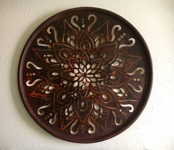 Up-cycled oil drum lid cut with a plasma torch. Beautiful mandala design and finished with a rust patina.