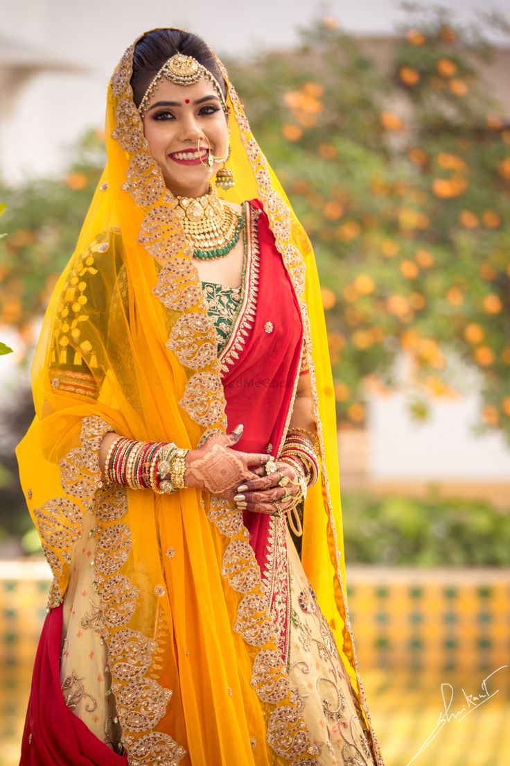 Colourful and bright wedding lehenga with a yellow and red dupatta and green blouse accompanied by an ivory lehenga skirt| WedMeGood||#wedmegood #indianweddings #weddingoutfits #bridallehenga #colourfullehenga #yellowdupatta #doubledupatta