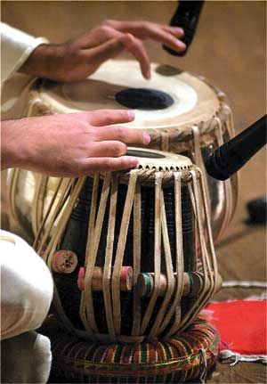 """The right hand fingering takes a while to learn. He's playing the bol """"Na"""" here and Ga on the tabla, together they are 'Dah'. The playing technique involves extensive use of the fingers and palms in various configurations to create a wide variety of different sounds and rhythms, reflected in the mnemonic syllables."""