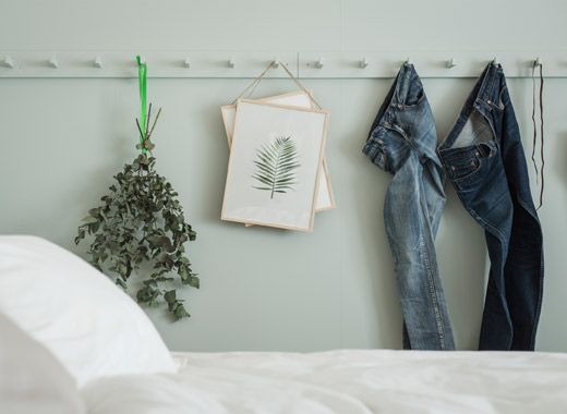 Jeans, dried plants and artwork hanging on hook racks painted the same light green colour as the bedroom wall