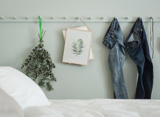 Džíny, sušené květiny a umělecká díla visí na háčcích natřených stejnou světle zelenou barvou jako stěny ložnice.